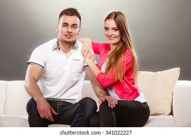 Portrait of smiling woman and man sitting on sofa posing. Happy joyful couple.