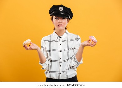 Portrait of smiling woman in plaid shirt and police cap posing on camera with donuts in hands isolated over yellow background