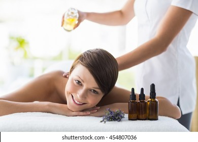 Portrait of smiling woman receiving massage treatment at spa