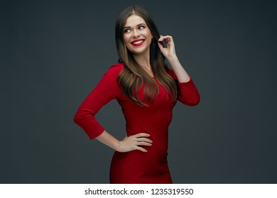 portrait of smiling woman in red dress isolated on dark background