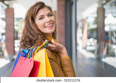 Portrait of smiling woman with shopping bags looking at camera at the shopping mall