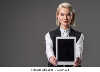 portrait of smiling woman showing tablet with blank screen isolated on grey