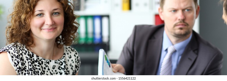 Portrait of smiling woman sitting with colleagues in office and discussing new start-up. Serious man listening attentively explaining of associate about statistics data. Business meeting concept
