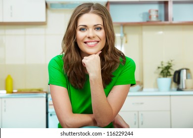 Portrait of smiling woman sitting in kitchen on a chair. Clothes of green color.