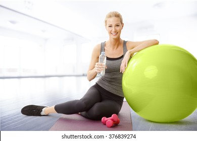 Portrait of smiling woman sitting next to fitness ball and holding in hand a bottle of water while relaxing after fitness workout.
