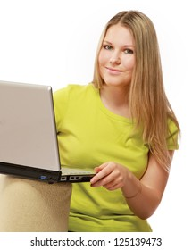 A portrait of smiling woman sitting on the sofa with a laptop