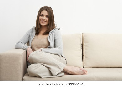 Portrait of smiling woman sitting on sofa. Casual style indoor shoot.