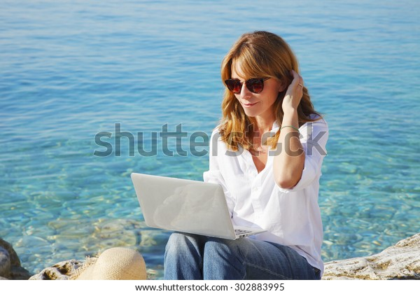 Portrait of smiling woman sitting at the rock by the see with her laptop and using private banking.