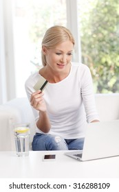 Portrait of smiling woman sitting at sofa in front of laptop and holding credit card in her hand while shopping online.