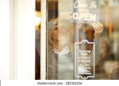 Portrait of smiling woman standing behind her clothing store shop window. Small business.