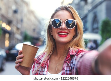 Portrait of smiling woman taking photo on the smartphone.