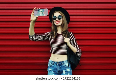 Portrait of smiling woman taking a selfie picture by smartphone on a red background