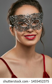 Portrait of smiling woman with tied back dark hair, wearing wine red crop top. The young girl is tilting her head, wearing silver carnival mask with perforation. Vintage women's carnival accessory.
