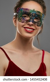 Portrait of smiling woman with tied back dark hair, wearing wine red crop top. The young girl is tilting head, wearing iridescent carnival mask with perforation. Vintage women's carnival accessory.