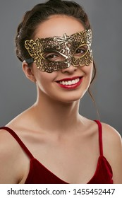 Portrait of smiling woman with tied back dark hair, wearing wine red crop top. The young girl is tilting her head, wearing golden carnival mask with perforation. Vintage women's carnival accessory.