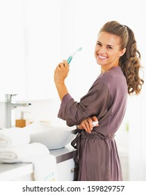 Portrait of smiling woman with toothbrush in bathroom