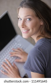 Portrait of a smiling woman using her laptop at home