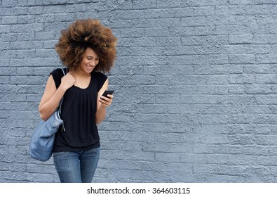 Portrait of smiling woman walking and looking at mobile phone