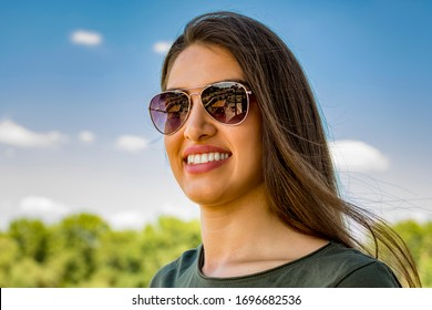 Portrait of a smiling woman wearing sunglasses outdoors