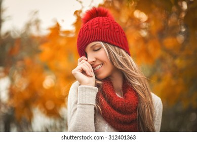 Portrait of smiling woman wearing woolen accessories. Young woman in beautiful autumn park, concept autumn