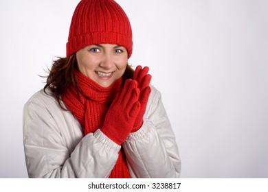 Portrait of a smiling woman with winter outerwear, clapping her gloved hands together. Isolated on white. Horizontal format.