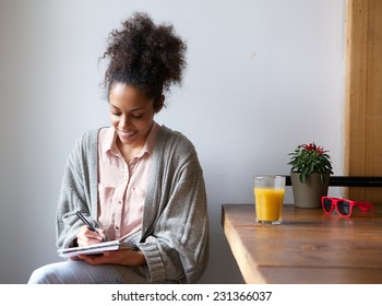Portrait of a smiling woman writing on note pad at home