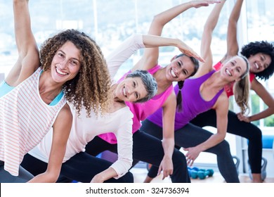 Portrait of smiling women bending with arms raised in fitness studio