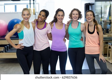 Portrait of smiling women standing together with arms around in gym