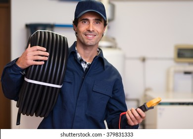 Portrait of a smiling worker carrying corrugated conduit and a tester