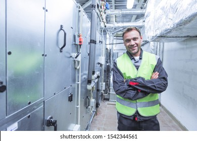 Portrait of smiling worker in electrical switchgear room of CNC plant