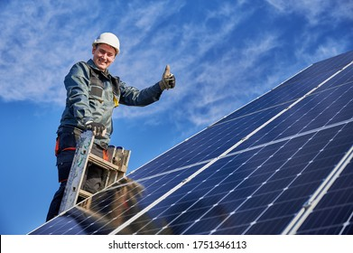 Portrait of a smiling worker, installing solar batteries, standing on ladder at solar plant against blue sky, showing thumb up. Concept of alternative energy and power