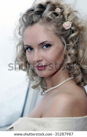 Portrait of smiling young adult bride with blond hairstyle.