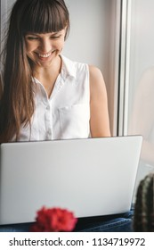 Portrait of smiling young adult woman sitting on windowsill with laptop looks at the monitor.