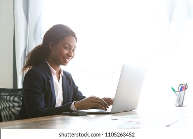 Portrait of smiling young african american business woman working laptop in office