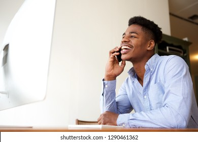 Portrait of smiling young african american businessman talking on phone while looking at computer