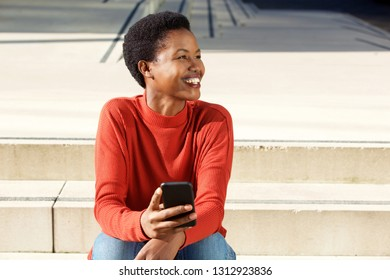 Portrait of smiling young african american woman sitting outside with mobile phone
