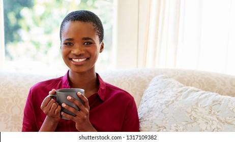 Portrait of a smiling young African American woman drinking a cup of coffee while relaxing on her living room sofa at home