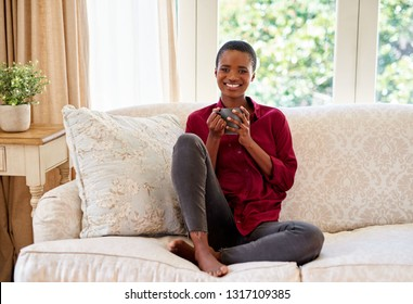 Portrait of a smiling young African American woman relaxing on her living room sofa at home and drinking a cup of coffee