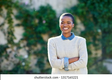 Portrait of a smiling young African American woman standing with her arms crossed outside in her yard on a sunny day in the summer