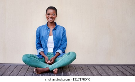 Portrait of a smiling young African American woman sitting alone on the floor of her patio outside