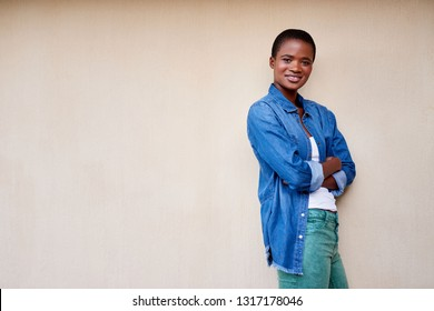 Portrait of a smiling young African American woman standing with her arms crossed on her patio outside
