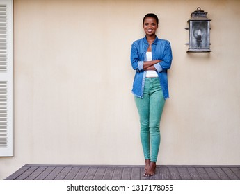 Portrait of a smiling young African American woman standing with arms her crossed on her patio outside