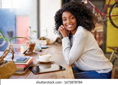 Porträt einer lächelnden jungen Afroamerikanerin, die an einem Fenster in einem Café mit Cappuccino und digitaler Tablette sitzt