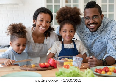 Portrait of smiling young african American family with little kids cooking together in kitchen at home, happy loving biracial parents teach small children prepare food make healthy salad dinner