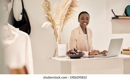 Porträt einer lächelnden jungen afroamerikanischen Unternehmerin, die an einem Laptop an einer Theke in ihrem Kleidungsgeschäft arbeitet