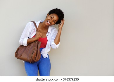 Portrait of smiling young african american woman carrying a bag standing against a wall