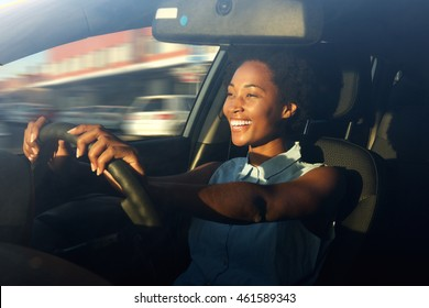 Portrait of smiling young african american woman driving a car