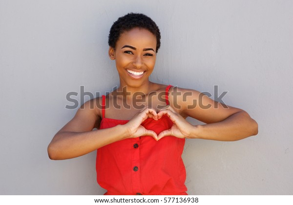 Portrait of smiling young african american woman with heart shape hand sign