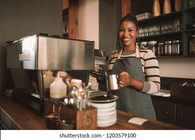 Portrait of a smiling young African barista frothing milk for a cappuccino behind the counter of her trendy cafe