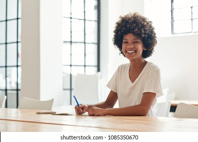 Portrait of a smiling young African female student with an afro writing in a notebook while sitting alone at a table on campus